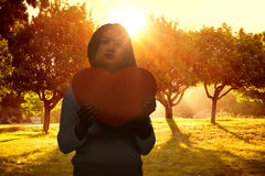 Composite image of asian woman holding paper heart Stock Photography