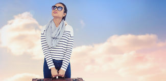 Composite image of asian woman with luggage looking up. Asian woman with luggage looking up against beautiful blue cloudy sky Stock Images