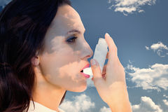 Composite image of asthmatic brunette using her inhaler. Asthmatic brunette using her inhaler against blue sky stock image