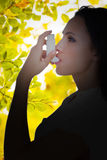Composite image of asthmatic brunette using her inhaler. Asthmatic brunette using her inhaler against detail shot of leaves royalty free stock photography