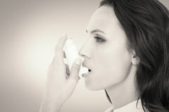 Composite image of asthmatic brunette using her inhaler. Asthmatic brunette using her inhaler against grey vignette stock photos