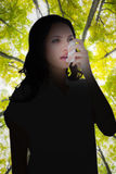 Composite image of asthmatic brunette using her inhaler. Asthmatic brunette using her inhaler against low angle view of tall trees stock photos