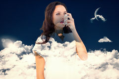 Composite image of asthmatic brunette using her inhaler. Asthmatic brunette using her inhaler against night sky royalty free stock image