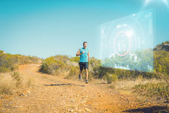 Composite image of athletic man jogging on country trail Royalty Free Stock Photos