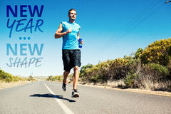 Composite image of athletic man jogging on open road holding bottle Royalty Free Stock Photography