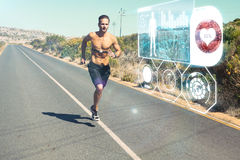 Composite image of athletic man jogging on open road with monitor around chest Stock Photos