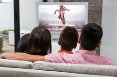 Composite image of athletic woman practicing show jumping. Athletic women practicing show jumping against happy family watching tv on the sofa Stock Images