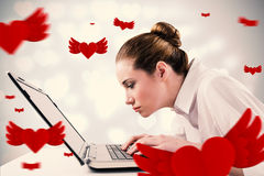 Composite image of attentive businesswoman typing on laptop Royalty Free Stock Photos
