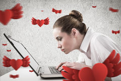 Composite image of attentive businesswoman typing on laptop Royalty Free Stock Image