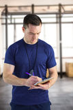 Composite image of attentive trainer writing on his clipboard Royalty Free Stock Photography
