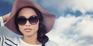 Composite image of attractive asian woman with hat and sunglasses Royalty Free Stock Images