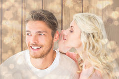 Composite image of attractive blonde whispering secret to boyfriend Royalty Free Stock Images