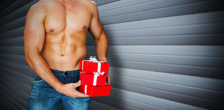 Composite image of attractive bodybuilder with gifts Stock Photos