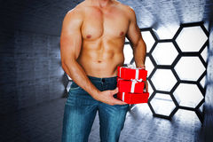 Composite image of attractive bodybuilder with gifts Stock Photography