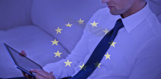 Composite image of attractive businessman using digital tablet. Attractive businessman using digital tablet against european flag Royalty Free Stock Image