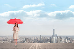 Composite image of attractive businesswoman holding red umbrella Stock Photo