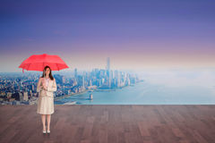 Composite image of attractive businesswoman holding red umbrella Royalty Free Stock Image