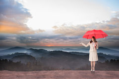 Composite image of attractive businesswoman holding red umbrella Stock Photos