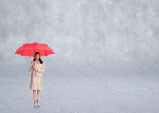 Composite image of attractive businesswoman holding red umbrella Stock Image