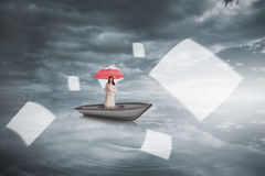 Composite image of attractive businesswoman holding red umbrella in a boat Royalty Free Stock Photos
