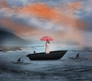 Composite image of attractive businesswoman holding red umbrella in a sailboat Stock Image