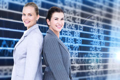 Composite image of attractive businesswomen standing back-to-back Royalty Free Stock Photo