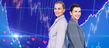 Composite image of attractive businesswomen standing back-to-back Royalty Free Stock Photography