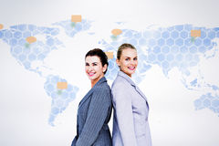 Composite image of attractive businesswomen standing back-to-back. Attractive businesswomen standing back-to-back against world map Stock Photo