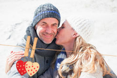 Composite image of attractive couple on the beach in warm clothing Royalty Free Stock Image