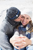 Composite image of attractive couple on the beach in warm clothing Stock Photos