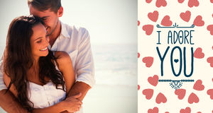 Composite image of attractive couple cuddling and valentines words. Attractive couple cuddling against valentines words Stock Photo