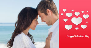 Composite image of attractive couple embracing on the beach Royalty Free Stock Image