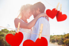 Composite image of attractive couple embracing by the road Stock Images