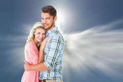 Composite image of attractive couple embracing and smiling at camera Stock Images