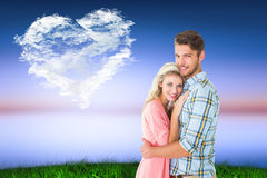 Composite image of attractive couple embracing and smiling at camera Royalty Free Stock Images