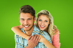 Composite image of attractive couple embracing and smiling at camera Royalty Free Stock Image