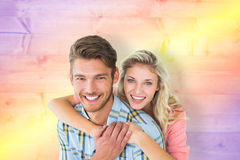 Composite image of attractive couple embracing and smiling at camera Stock Photos