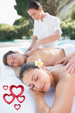 Composite image of attractive couple enjoying couples massage poolside Stock Photography