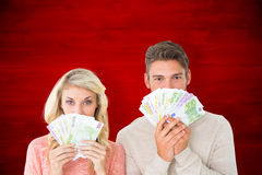 Composite image of attractive couple flashing their cash Stock Image