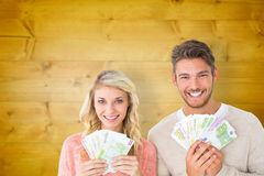 Composite image of attractive couple flashing their cash Royalty Free Stock Images