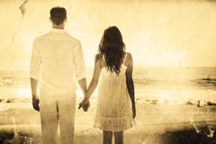 Composite image of attractive couple holding hands and watching the ocean Royalty Free Stock Photos