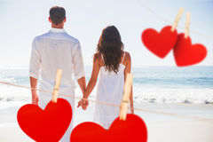 Composite image of attractive couple holding hands and watching the ocean Stock Images
