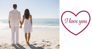 Composite image of attractive couple holding hands and watching the waves. Attractive couple holding hands and watching the waves against valentines love hearts royalty free stock images