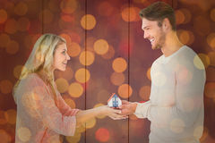 Composite image of attractive couple holding miniature house model Royalty Free Stock Photos