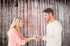 Composite image of attractive couple holding miniature house model Stock Photo