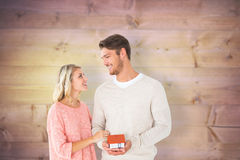 Composite image of attractive couple holding miniature house model Stock Image