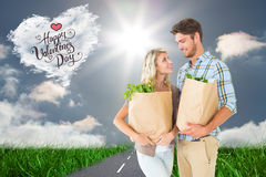 Composite image of attractive couple holding their grocery bags Stock Photo