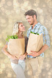 Composite image of attractive couple holding their grocery bags Stock Image