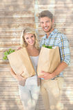 Composite image of attractive couple holding their grocery bags Stock Images