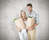 Composite image of attractive couple holding their grocery bags Royalty Free Stock Images